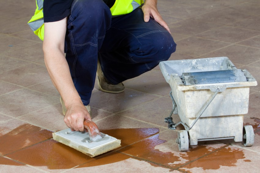 Construction worker cleaning newly build in floor tiles.