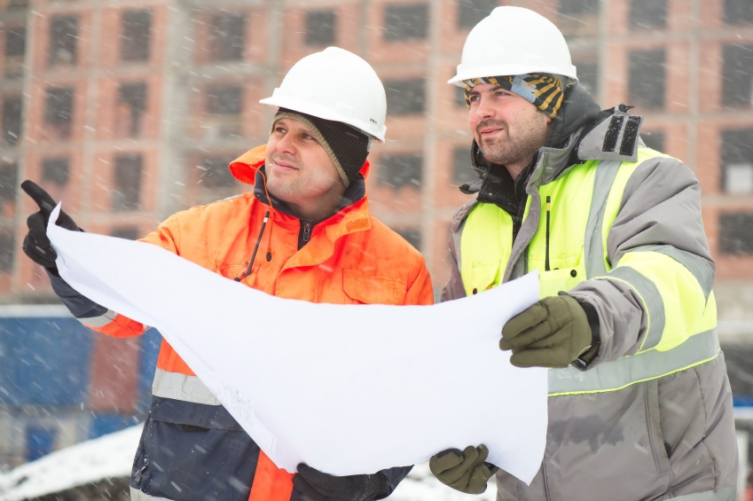 Two male construction workers wearing safety gloves, hat and jacket